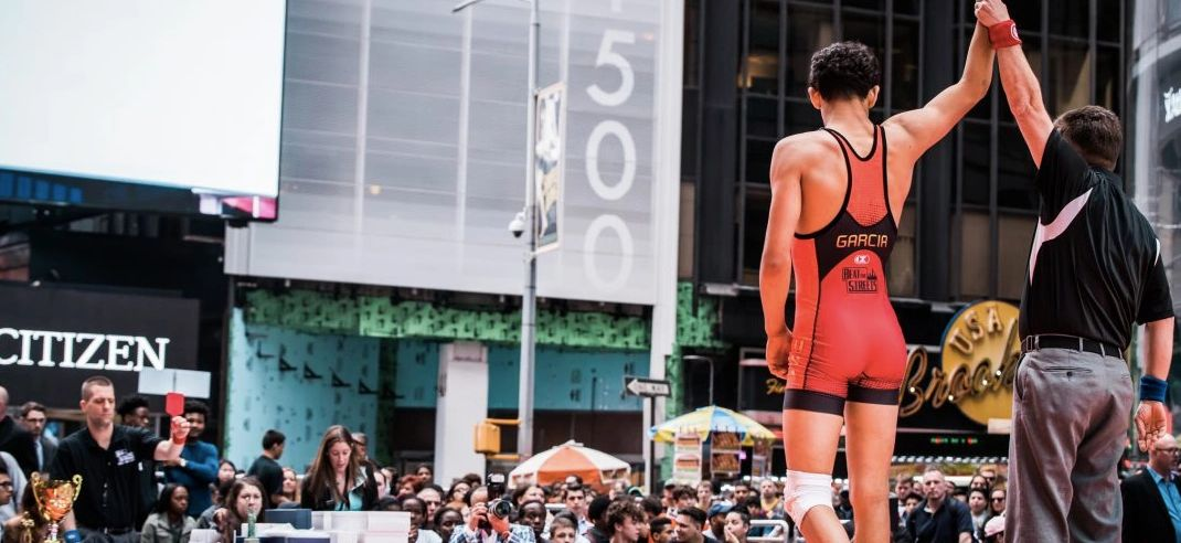 Angel Garcia gets his hand raised in Times Square following a win at the Beat the Streets New York Gala in 2016. On Friday, Garcia delivered a historic win to become the first male wrestler from a Beat the Streets program to win a Junior national title. (Photo by James Mangan, Beat the Streets Philadelphia)